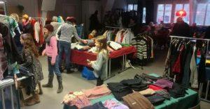 Das Bild zeigt den Veranstaltungsraum der Klimawerkstatt Werder bei der Kleidertauschparty mit Menschen, die sich an verschiedenen Tischen Kleidungsstücke ansehen.