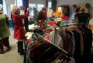 Das Bild zeigt Menschen, die Kleidung von einem Tisch und Kleiderständer bei der Kleidertauschparty der Klimawerkstatt Werder begutachten.