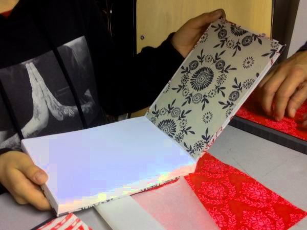 Auf diesem Bild ist zu sehen, wie Bücherrohlinge mit Stoff verkleidet werden.