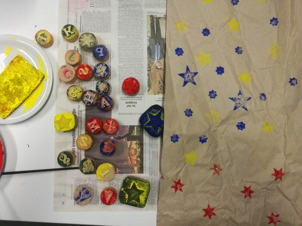 Auf dem Bild sind Stempel und selbst gestempeltes Geschenkpapier auf Altpapier in der der Klimawerkstatt Werder zu sehen.