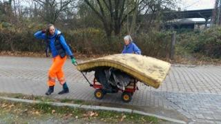 Auf dem Bild ziehen zwei Personen einen Bollerwagen, der mit Müllsäcken und sogar einer alten Matratze beladen ist. Der Müll wurde beim Müllsammelspaziergang der Klimawerkstatt Werder am 25.11.2018 eingesammelt.